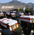 Turkish soldiers from a military guard of honor carry coffins during a  mass burial ceremony for Turkish Cypriots who went missing in 1974 and whose remains have been found by the committee on missing  people in Cyprus, on August 15, 2016 at a cemete