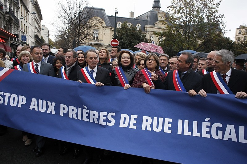 Clichy la Garenne's mayor Remi Muzueau, center left, leads the demonstration against Muslim street prayers, in the Paris suburb of Clichy la Garenne, Friday, Nov. 10, 2017. (AP Photo)