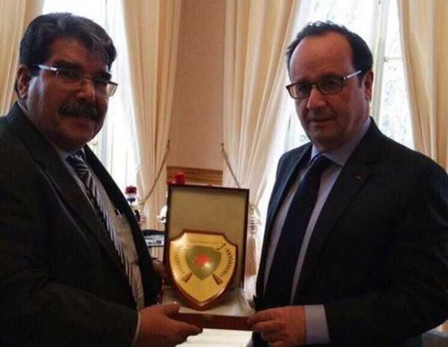 Terrorist Salih Muslim L presenting a plaquet to French President Hollande