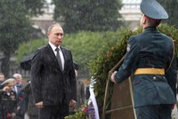 Ignoring the torrential rain, Russian President Vladimir Putin remained standing with a firm expression at the Tomb of the Unknown Soldier in Moscow Thursday.