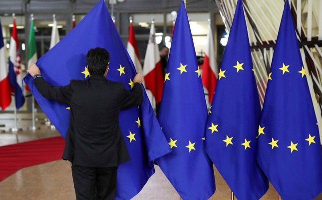 A staff member adjusts flags prior to the extraordinary EU leaders summit to finalize and formalize the Brexit agreement with the UK in Brussels, Belgium, Nov. 25, 2018. (Reuters Photo)
