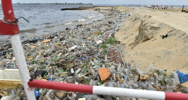 Plastic bottles and other waste lie on the sand after being washed ashore near the port of Abidjan on August 5, 2015 despite efforts by the government to promote a greener economy by banning plastic bags. (AFP Photo)