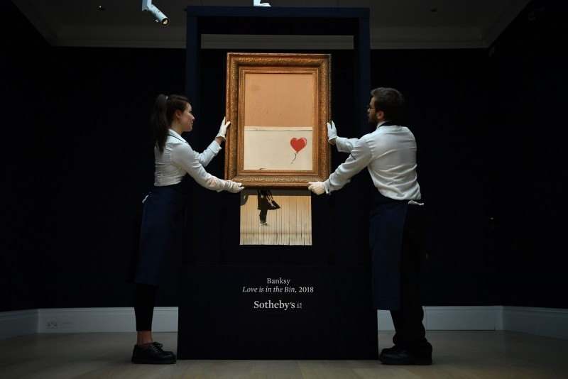 Sotheby's employees pose with the newly completed work by artist Banksy entitled ,Love is in the Bin, at Sotheby's auction house in London on October 12, 2018. (AFP Photo)