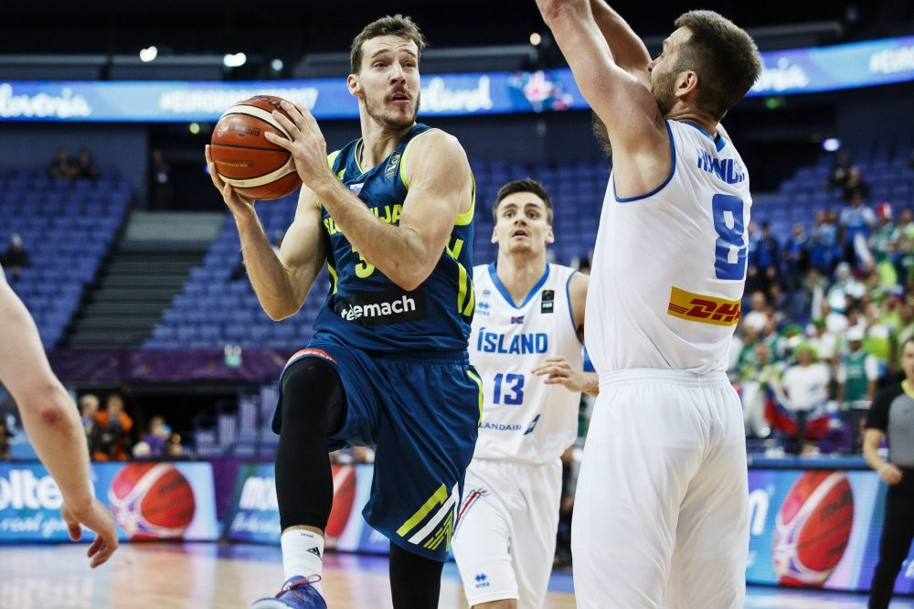 Goran Dragic of Slovenia vies with Hlynur Baeringsson of Iceland while Hordur Vilhjalmsson of Iceland looks on.
