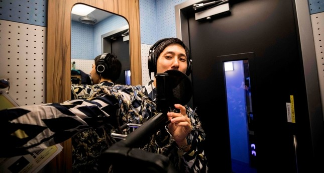In this photo taken on September 26, 2018, 33-year-old Japanese man Masaki Kitakoga sings alone in a tiny booth at a karaoke parlor in Tokyo. (AFP Photo)
