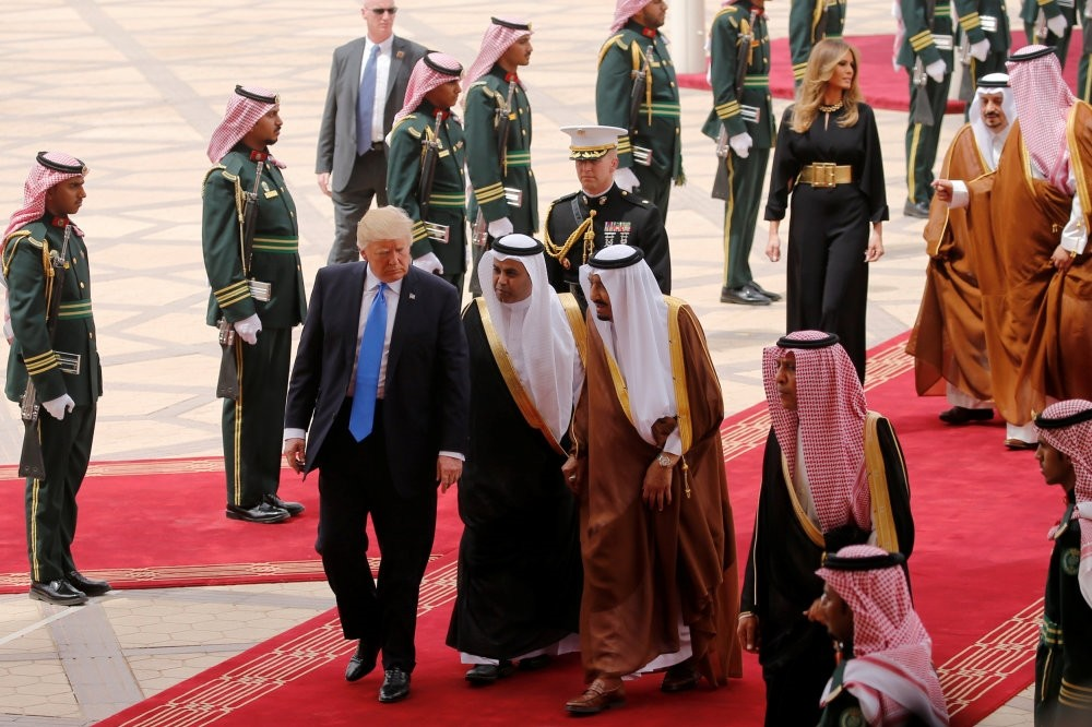 Saudi Arabia's King Salman (C, in brown and white) welcomes President Trump with a military honor cordon after they arrived the King Khalid International Airport in Riyadh, Saudi Arabia, May 20.