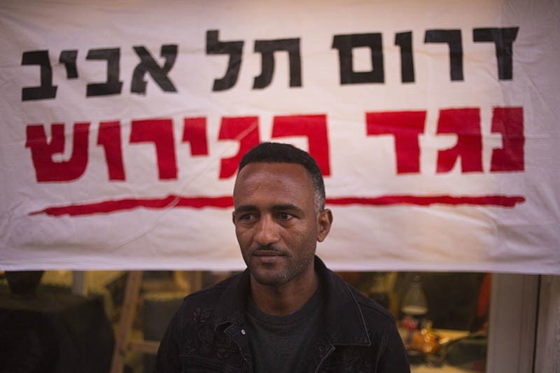 In this Tuesday, April 3, 2018 photo, Eritrean Halofom Sulta sits under a banner ,South Tel Aviv against deportation, after speaking to the Associated Press in southern Tel Aviv, Israel. (AP Photo)