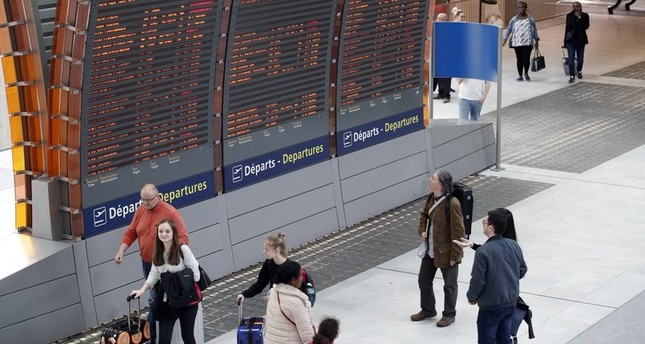 Travelers look at departure boards at Paris Charles de Gaulle airport, in Roissy, near Paris, Saturday, April 7, 2018. (AP Photo)
