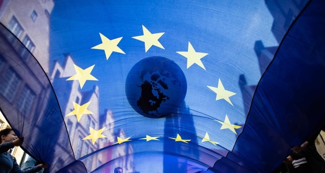 Protesters transport an inflated globe and a flag of the European Union through the streets during a demonstration, Muenster, northwestern Germany, May 24, 2019.