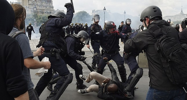 Police officers clash with a demonstrator near the Invalides during a protest against proposed labor reforms in Paris on June 14, 2016 (AFP).