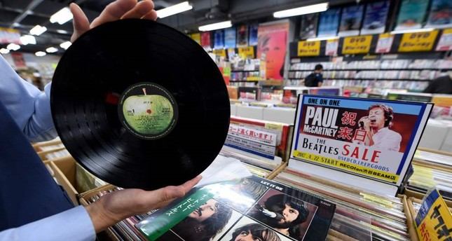 "A shop manager shows off a period Japanese pressing of The Beatles' final studio album ""Let It Be"" at the RECO fan music shop in Tokyo's Shibuya district."