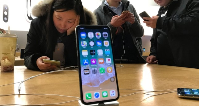 In this Nov. 6, 2017, file photo, shoppers check out the iPhone X at an Apple store in Beijing, China. (AP Photo)