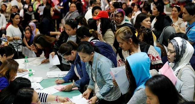 Filipino household workers who were repatriated from Kuwait show their documents as they arrive at Manila's international airport, Philippines, 21 February 2018. (EPA Photo)