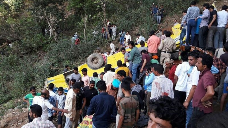 Onlookers rushed to search the mangled yellow bus upturned on the valley slope for survivors (AFP Photo)