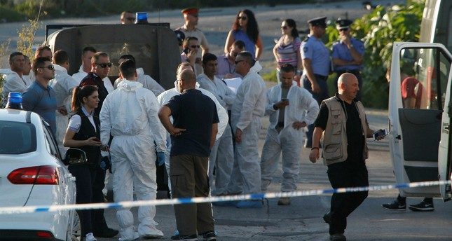 Police and forensics experts stand behind a road block after a powerful bomb blew up a car killing investigative journalist Daphne Caruana Galizia in Bidnija, Malta, October 16, 2017. (Reuters Photo)