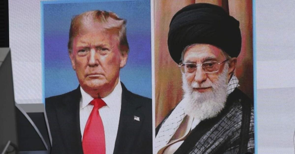 A man walks by a huge screen showing U.S. President Donald Trump (L) and Iranian Supreme Leader Ali Khamenei, Tokyo, Jan. 8, 2020. (AP Photo)