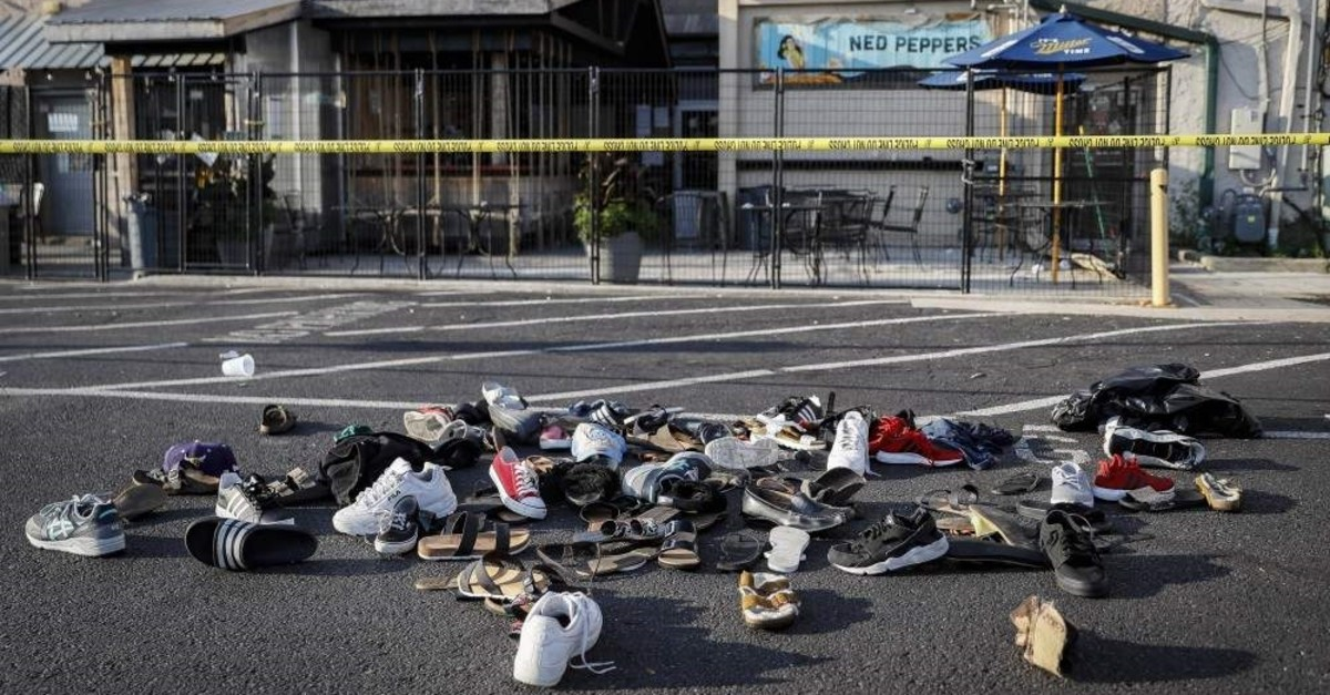 In this Sunday, Aug. 4, 2019, file photo, shoes are piled outside the scene of a mass shooting in Dayton, Ohio. (AP Photo)