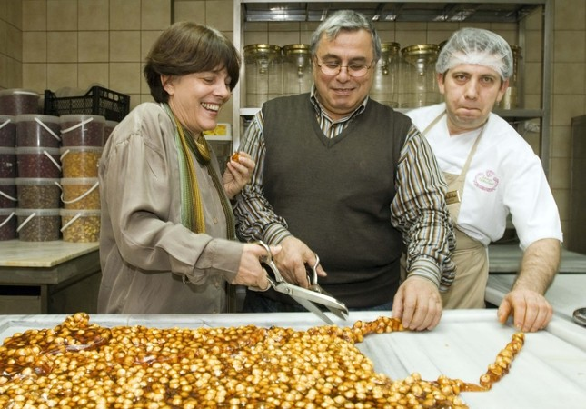 Mary Işın (L) helps chefs cut a traditional Ottoman sweet into pieces.