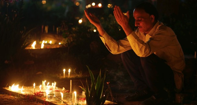 A Kashmiri Muslim prays as he lights candles at the grave of his relative to mark Shab-e-Barat, one of the holiest nights on the Islamic calendar.