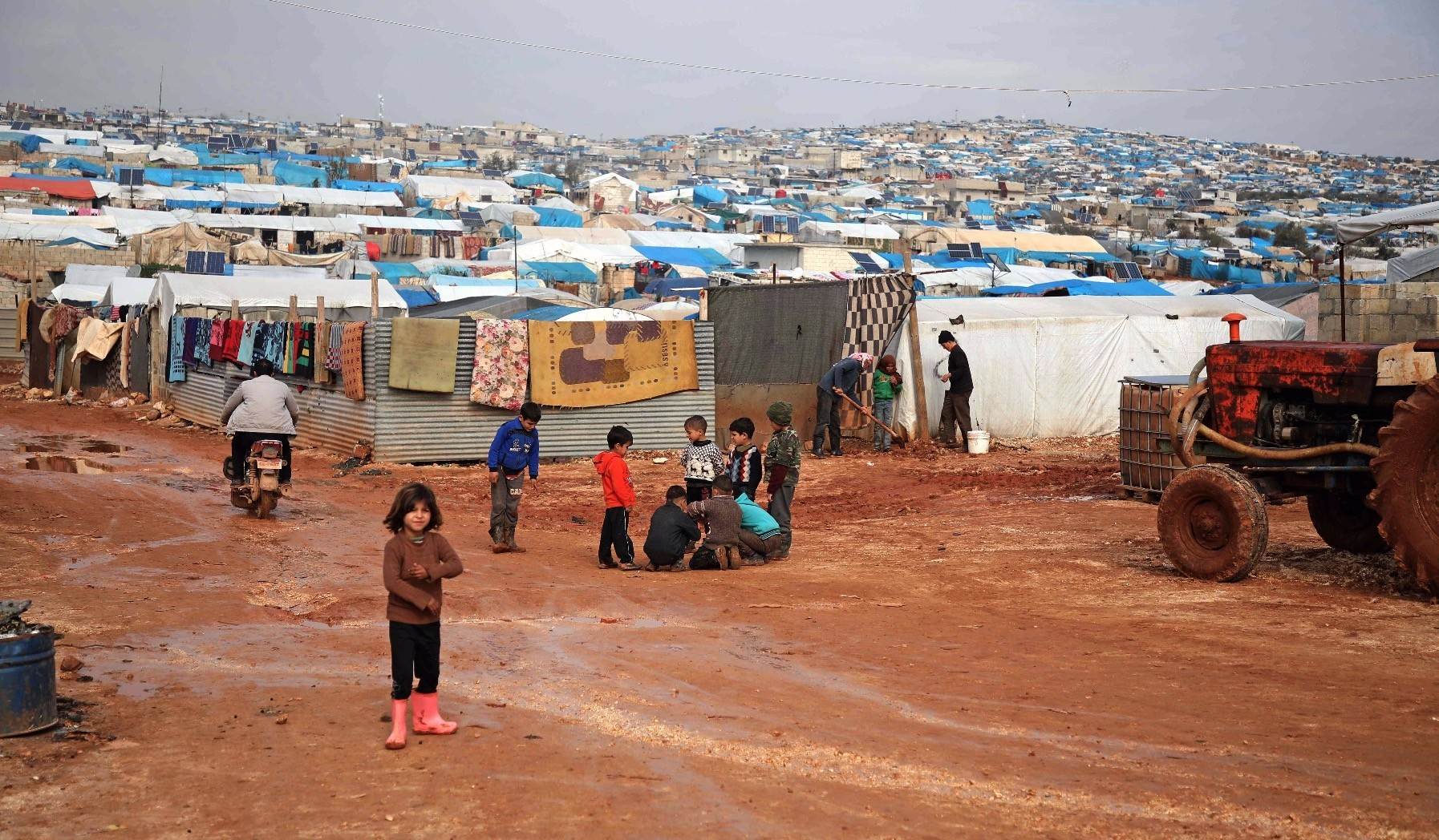 Children gather outside their makeshift shelters following torrential rain that affected a camp for displaced people near the town of Atme, close to the Turkish border, in Syriau2019s mostly opposition-held northern Idlib province, Jan. 10.