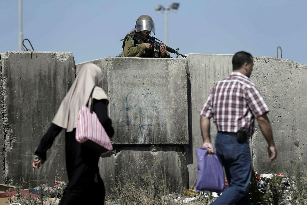 A female Israeli soldier stands guard at the Qalandia checkpoint, south of Ramallah, West Bank.
