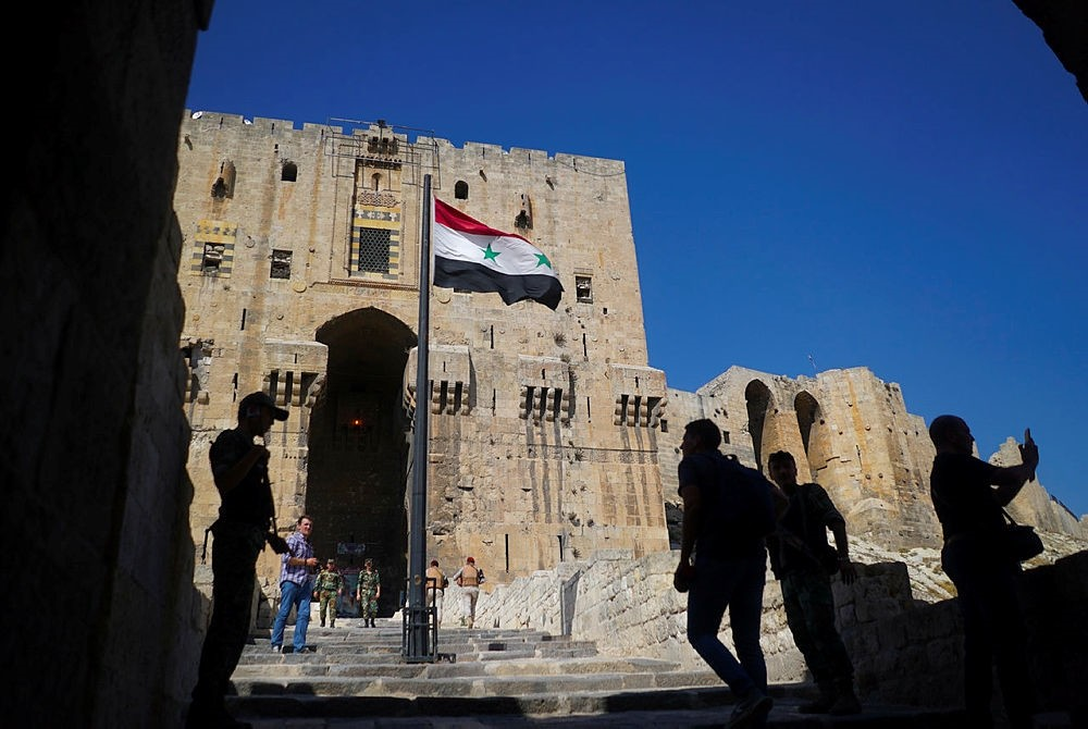 Visitors and Russian military police officers walk toward the Citadel, Aleppo's famed fortress. (AP Photo)