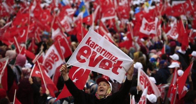 A supporter of the 'yes' campaign waving a banner, reading 'Kararımız evet' which is translated in English as 'Our decision is Yes' referring to the April referendum, during a rally in the northern city of Rize, April 3.