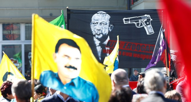 PKK supporters holding a placard picturing President Erdoğan with a gun pointed to his head and a flag picturing imprisoned PKK leader, Abdullah Öcalan, along with the terrorist group's flags during the demonstration in Swiss city of Bern, March 25.