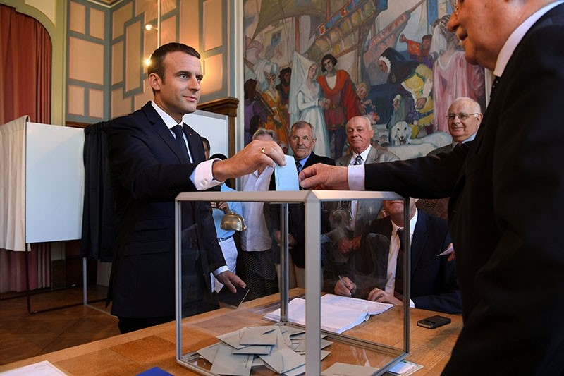 French President Emmanuel Macron (L) casting his vote in the second round of the French legislative elections at the City Hall in Le Touquet, France, 18 June 2017. (EPA Photo)