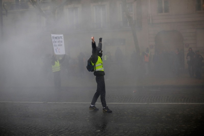 A demonstrators raises his arms amid tear gas during a yellow vest protest Saturday, Jan. 19, 2019 in Paris. (AP Photo)