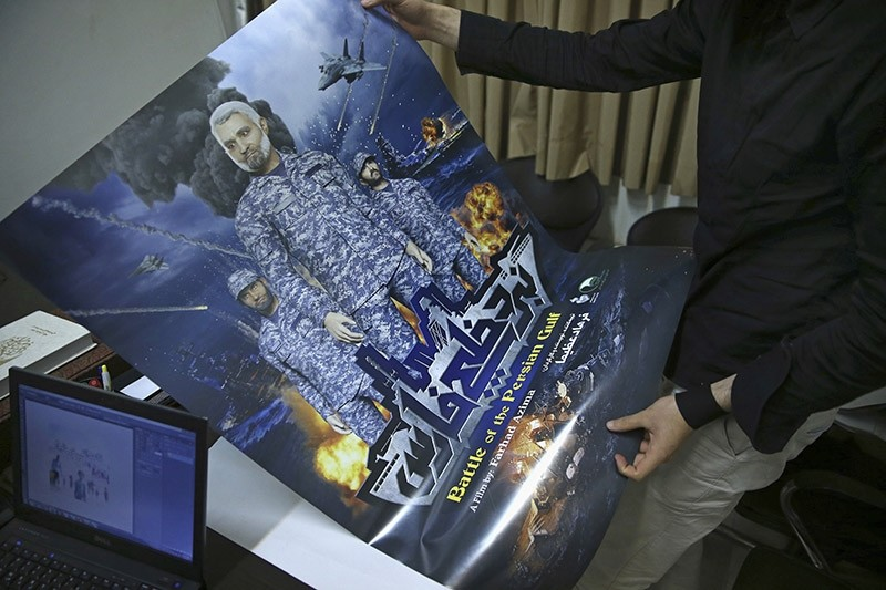 A production assistant for the animated film, ,Battle of the Persian Gulf II,, holds a poster for the movie, at the office of Farhad Azima in Tehran. (AP Photo)