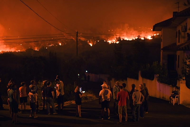 Villagers of Rio de Moinhos in Abrantes stand on the streets watching following a new rash of forest fires ahead of a weekend of warm temperatures, at Rio de Moinhos village in Abrantes on August 11, 2017. (AFP Photo)