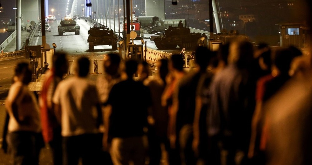 A crowd of civilians look at the pro-coup troops occupying a bridge in Istanbul on July 15, 2016.