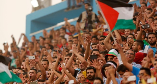 In this Sept. 8, 2015 file photo, Palestinian fans cheer during a World Cup soccer qualifying match between the Palestinian and the UAE teams at the Faisal al-Husseini stadium in the West Bank town of Al-Ram. AP Photo