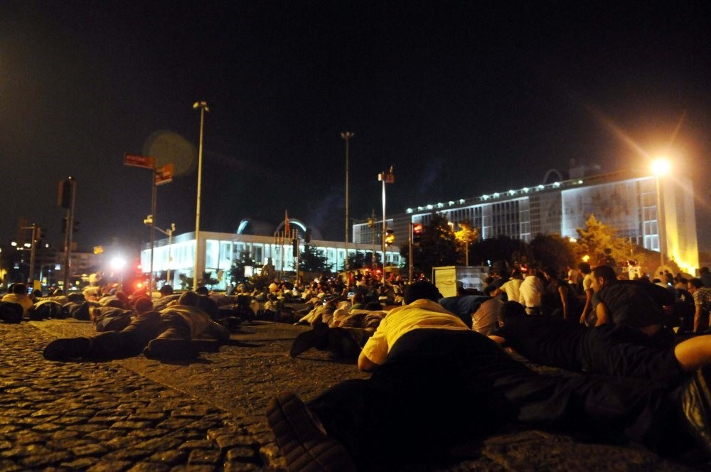 People take cover after soldiers open fire on an anti-coup crowd outside the Istanbul municipality building on July 15, 2016.