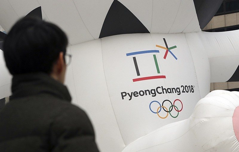 A man walks by the official emblem of the 2018 Pyeongchang Olympic Winter Games, in downtown Seoul, South Korea (AP Photo)