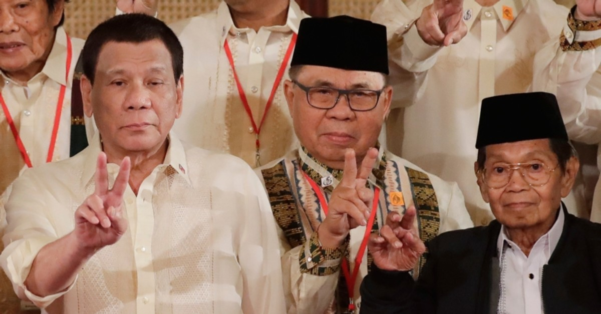 President Rodrigo Duterte, left, and Murad Ebrahim, Chairman of MILF, center, gesture following oath-taking ceremony for the creation of the Bangsamoro Transition Authority at the Presidential Palace in Manila, Philippines, Feb. 22, 2019. (AP Photo)