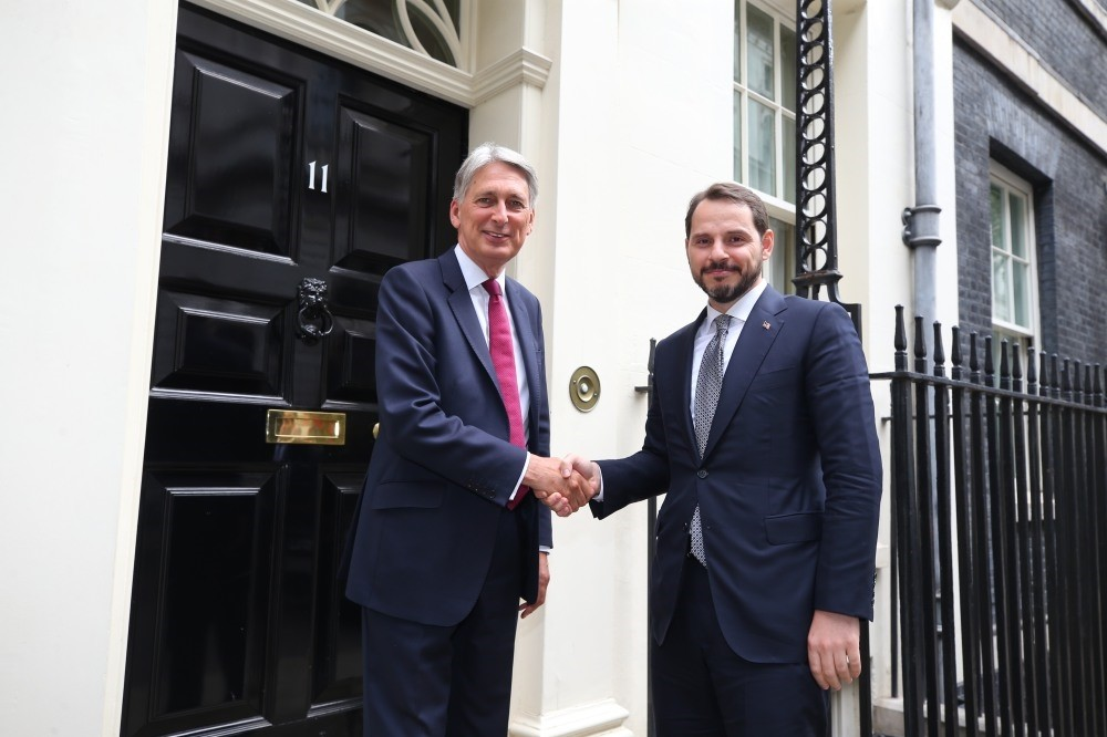 Treasury and Finance Minister Berat Albayrak and his British conterpart Philip Hammond (L) shake hands ahead of their meeting in London, Sept. 3.