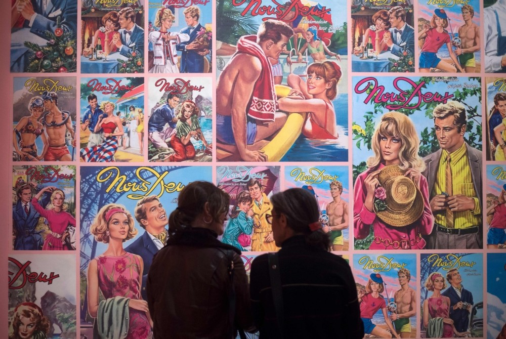 Women stand in front of covers of the photo novel ,Nous Deux, during a press preview of the exhibition ,Roman-Photo.,