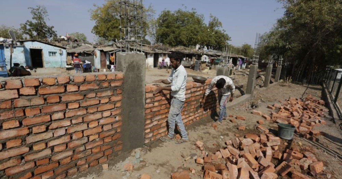 Indian workers construct a wall in front of a slum ahead of U.S. President Donald Trump's visit, in Ahmadabad, India, Monday, Feb. 17, 2020. Trump is scheduled to visit the city during his Feb. 24-25 India trip. (AP Photo)