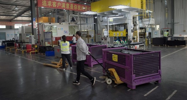 A worker pulls a trolley containing car interior pieces for a major European car maker in the American Industrial Park in Shenyang.