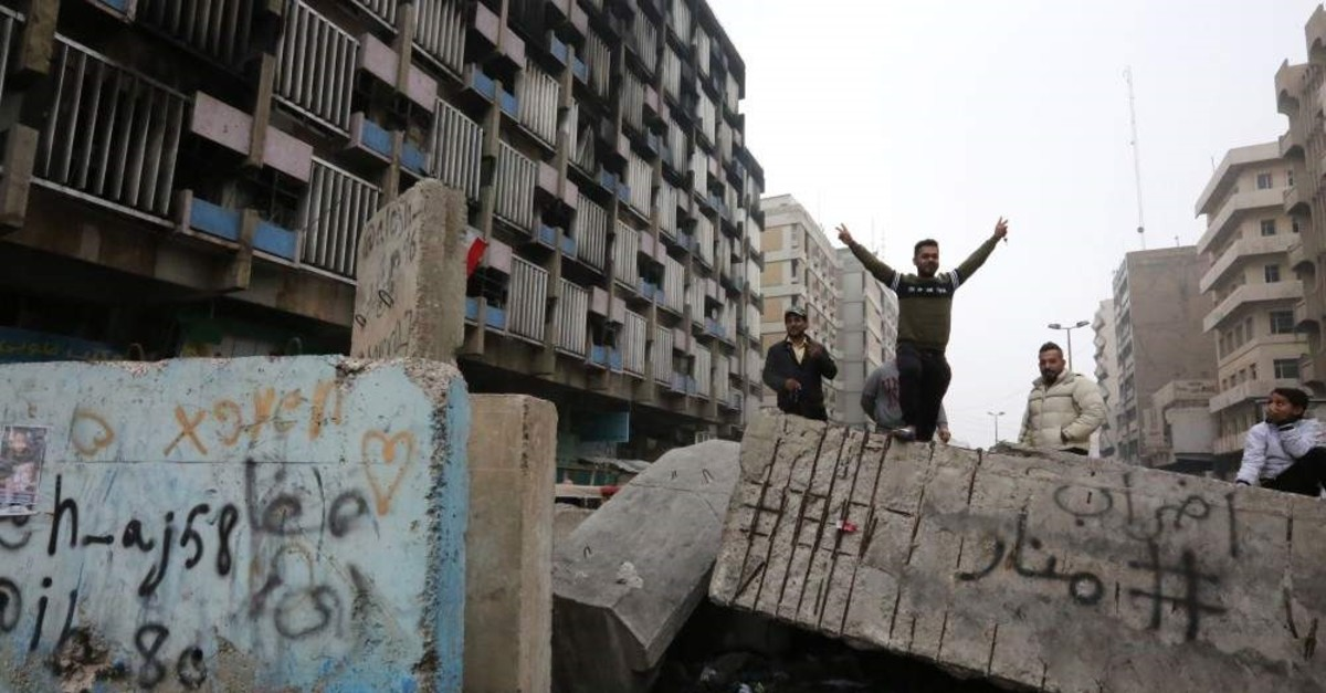 An Iraqi protester gestures as he stands on a cement block at Al-Khilani square, Baghdad, Dec. 7, 2019. (AFP Photo)