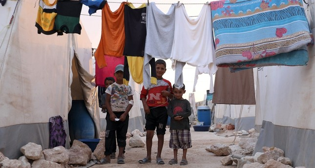 """Displaced Syrian children pose for a photograph in the camp """"Hope"""" in Kafaldin on the Syrian-Turkish border, Sept. 13."""