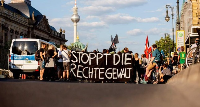 People hold up a banner that reads Stop the right-wing violence during a march, Berlin, June 18, 2019.