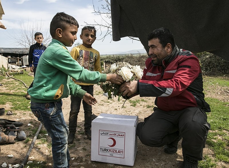 A children gives flowers to a Turkish Red Crescent worker in Nasiriyah village near the town of Jandaris, southern Afrin, Syria, on March 11, 2018. (AA Photo)