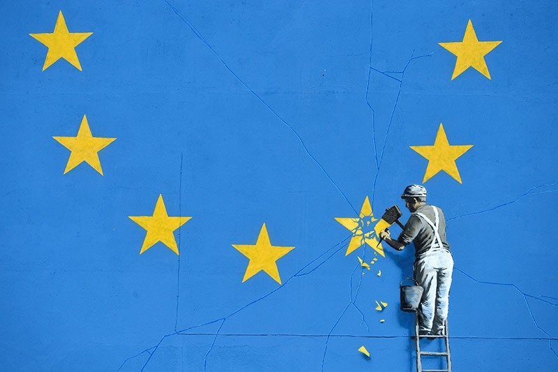 A section of an artwork attributed to street artist Banksy, depicting a workman chipping away at one of the 12 stars on the flag of the European Union, is seen on a wall in the ferry  port of Dover, Britain (Reuters Photo)