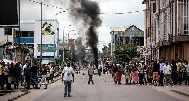 People look on as protesters burn tires during a demonstration calling for the President of the Democratic Republic of the Congo (DRC) to step down on Jan. 21, 2018 in Kinshasa. (AFP Photo)
