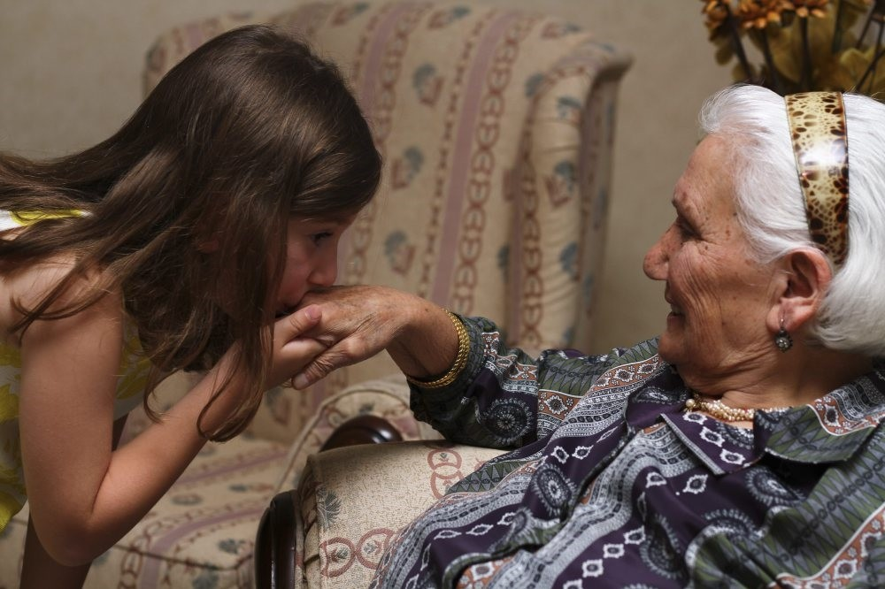 A little girl kissing the hand of her grandmother which is a custom during the religious holidays in Turkey.