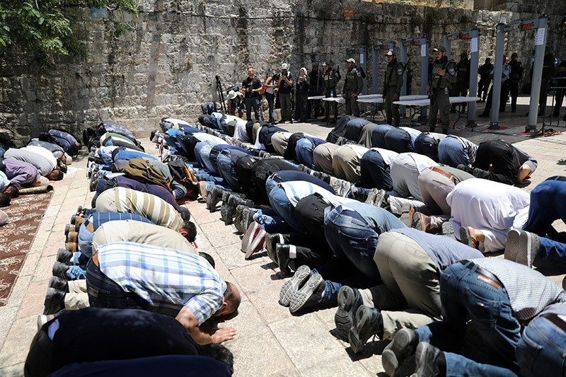 Palestinians pray as Israeli police officers look on by newly installed metal detectors at entrance to compound known to Muslims as Haram al-Sharif (Noble Sanctuary) and to Jews as Temple Mount in Jerusalem's Old City, July 16, 2017. (Reuters Photo)