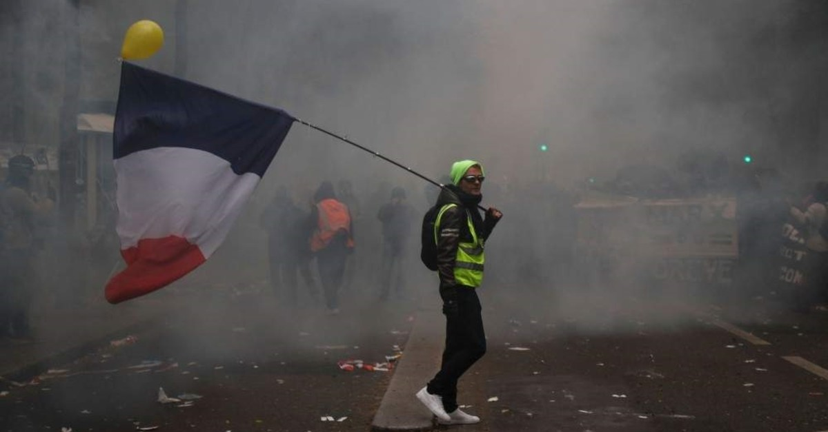 A man in a yellow vest holding a French flag walks through tear gas as part of a nationwide strike, Paris, Dec. 5, 2019. (AFP Photo)